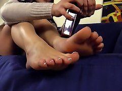 Cardigan cutie rubs lotion into her gorgeous feet
