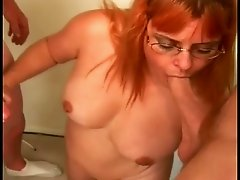 Nasty MILF in glasses sucks two dicks and gets facialed